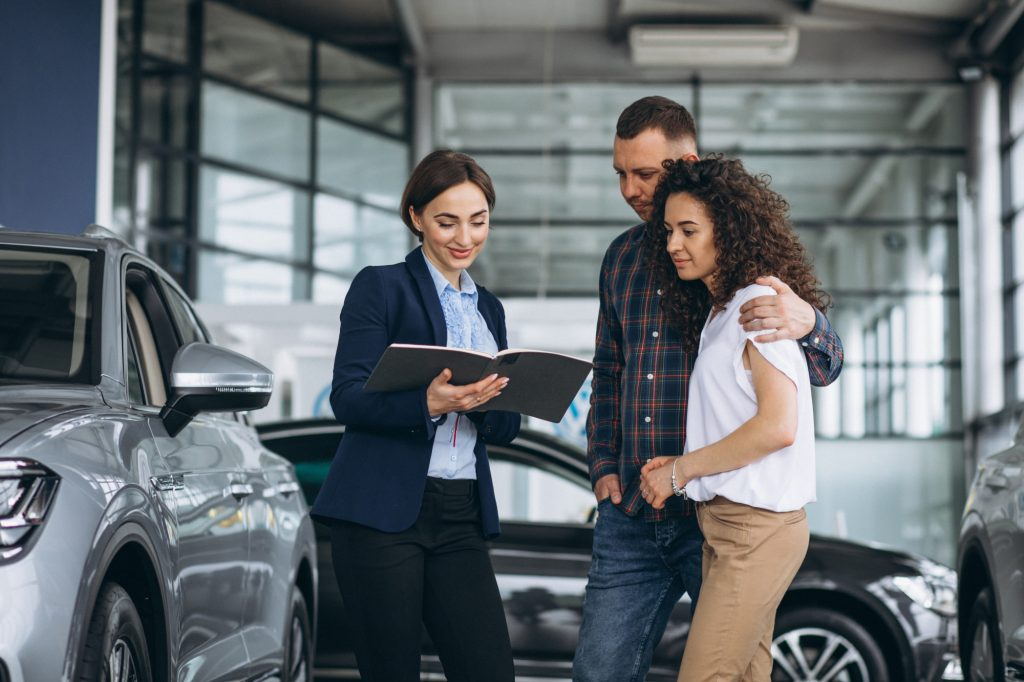 young-couple-talking-sales-person-car-showroom